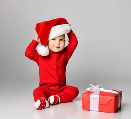 Little child boy toddler in santa claus christmas costume and hat happy smiling ready to celebrate...