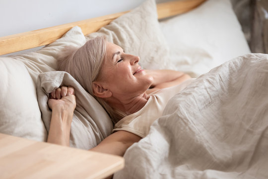 Satisfied middle-aged woman lying in bed enjoy early morning