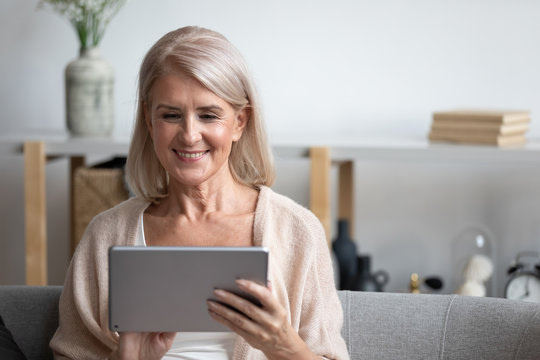 Attractive 60s woman sitting on couch with tablet computer