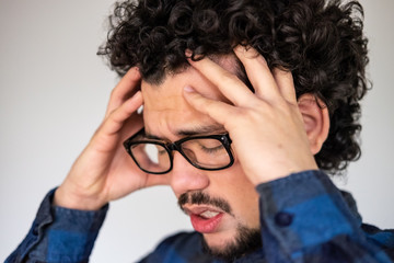 Latin American man with curly hair having a headache, upset expression, on a white background