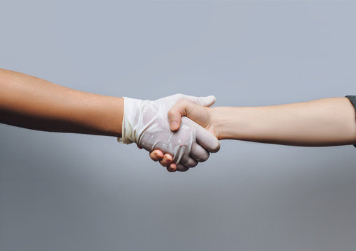 A young doctor in a white glove shakes hands with his patient. The concept of interaction and successful treatment. Gray background, copy space. Gynecology.