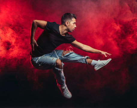 portrait of vigorous dancer male dancing street dance, jump in the air isolated over smoky background