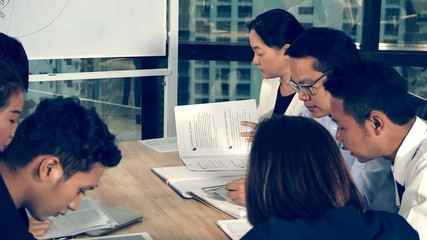 Asian business people discuss marketing strategy in group meeting at modern office. Business...