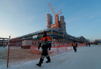 Construction workers walk past facilities of Amur gas processing plant under construction, part of Gazprom's Power Of Siberia project outside the far eastern town of Svobodny