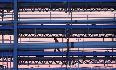 Construction worker walks along a bridge with pipelines at the construction site of Amur gas processing plant, part of Gazprom's Power Of Siberia project outside the far eastern town of Svobodny