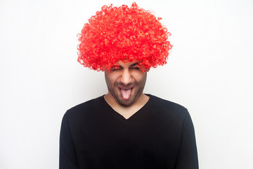 Portrait of funny crazy bizarre man with bristle and curly red wig sticking out tongue, making childish disobedient grimace, teasing and fooling around. indoor studio shot isolated on white background