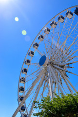 Ferris wheel, blue sky and sun flare, fun attraction at Cape Town, South Africa