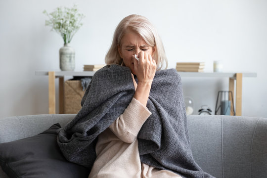 Aged sick woman sneezing holding napkin blow out runny nose