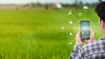 A male farmer is working in the field his using a mobile phone with Innovation technology for smart...