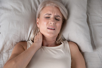 Above lying middle-aged woman feeling pain in neck