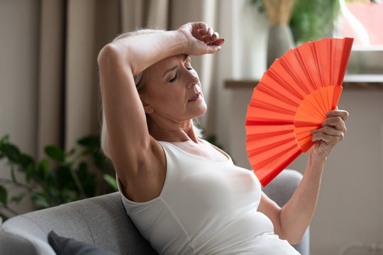 Middle-aged woman cooling herself with hand fan indoors