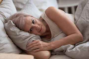 Sad elderly woman lying in bed suffers from insomnia