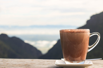 Hot chocolate in a glass cup on a wooden terrace with mountain view background in the morning light.