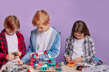 caucasian friends kids studying engineering, robotics, try to assemble robots, complex...