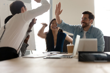 Multi-ethnic businesspeople giving high five celebrating closing profitable deal