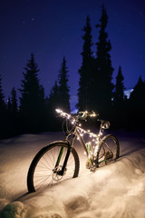 Bicycle decorated with Christmas lights at snow forest