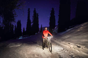 Man with bicycle at winter forest at night