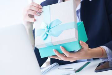 Christmas, any holiday. Office employee received a gift from her colleagues. Closeup woman hands holds gift box on office background.