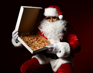 Santa Claus in aviator sunglasses is holding a box with big hot tasty pizza, showing us. New year Christmas fast food