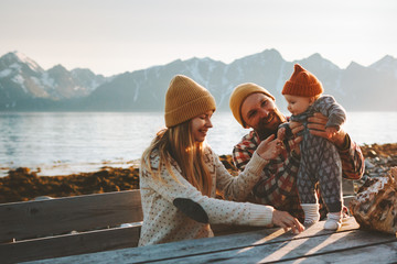Happy family outdoor mother and father with baby traveling together vacation parents playing with child healthy lifestyle mountains view in Norway Fotomurales