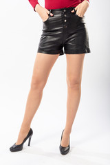 girl in leather black shorts and red jacket on a white background close-up, naked female legs in patent black heels
