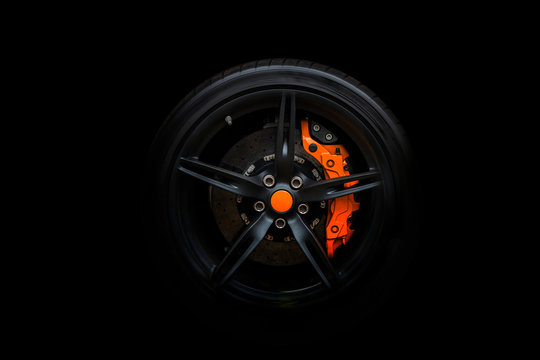 Isolated generic sport car wheel with orange breaks a black background