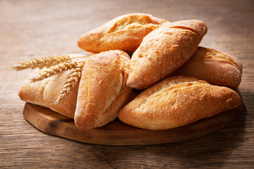 fresh bread with wheat ears on a wooden board