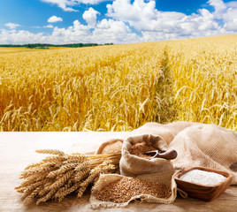 wheat ears, grains and flour on a wooden table on wheat field background