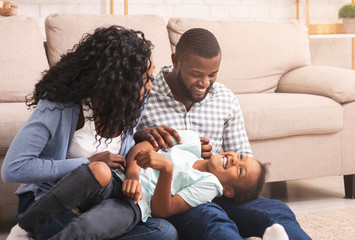 Loving afro parents tickling their little daughter, having fun at home