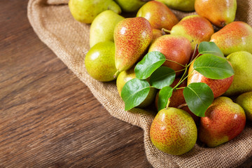 fresh pears with leaves on a wooden table