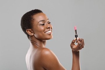 Attractive black woman holding pink lipstick over grey studio background Wall mural