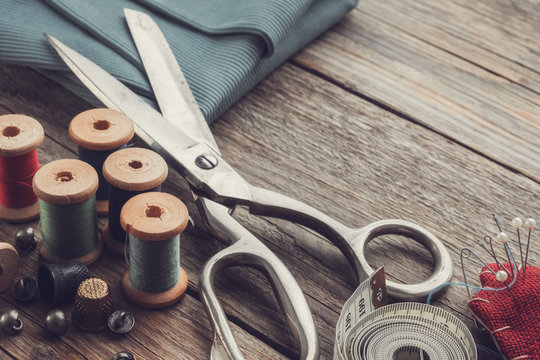 Retro sewing items: tailoring scissors, cutting knife, thimble, wooden thread spools, cushion for including pins, fabrics and sewing accessories.