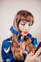 Seductive girl in retro style with modern technology - meeting of different eras - vintage and smartphone
