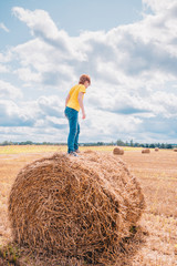 Childhood - caucasian happy child boy in jeans and yellow t-shirt playing on sunny field