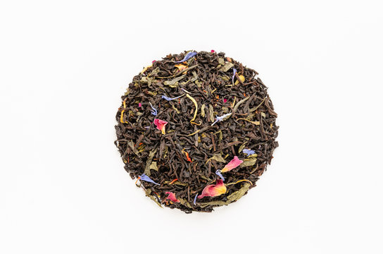 Dried tea leaves with herbal additives on white background. Blend of green and black tea with petals of cornflowers, roses, calendula, safflower. Healthy natural drinks concept. Close-up. Top view