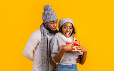 Happy afro winter girl holding Christmas gifts, boyfriend staying behind