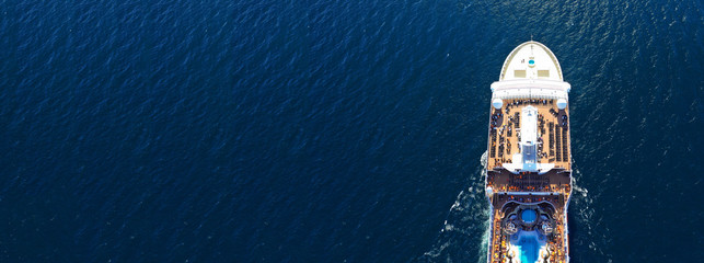 Aerial drone panoramic photo of huge cruise liner ship with top deck swimming pool cruising open ocean sea