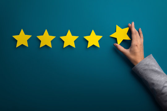 Woman hand giving five star rating on green