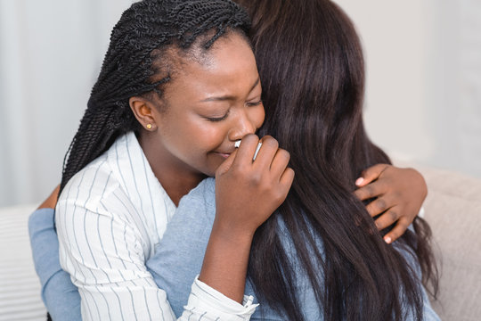 Girl hugging and consoling her crying friend at home