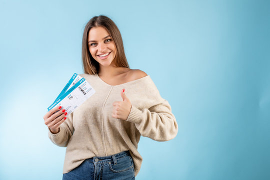 woman with boarding pass plane tickets showing thumbs up and smiling isolated over blue