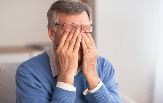 Senior Man Massaging Tired Eyes Sitting On Couch At Home