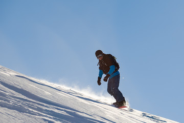 Snowboarder Riding Red Snowboard in Mountains at Sunny Day. Snowboarding and Winter Sports
