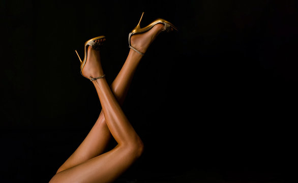 Sexy woman legs. Woman legs in gold shoes in black background with copy space. Long legs woman with high heels shoes.