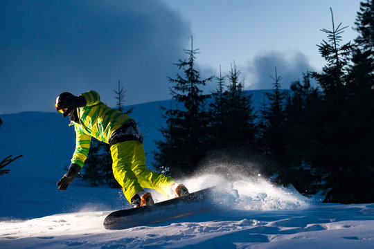 Snowboarder Riding Snowboard in the Forest at Night. Snowboarding and Winter Sports