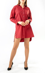 brunette in a red short tunic with long slender bare legs in black high heeled shoes on a white background
