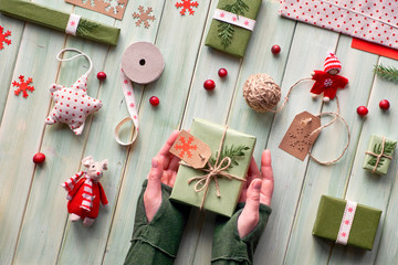 Various Christmas or New Year winter holiday eco friendly decorations, craft paper packages and handmade or zero waste gifts. Flat lay on wood, hands hold gift box decorated with green leaves.
