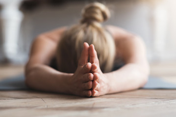 Woman laying face down on yoga mat, meditating