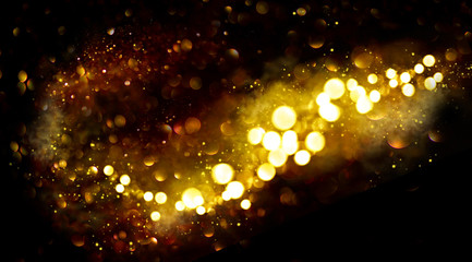 Golden Christmas and New Year glittering stars swirl on black bokeh background, backdrop with...