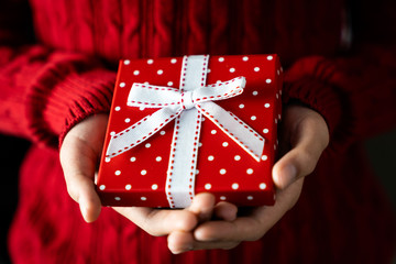 Young female hands holding Christmas gift with ribbon