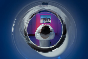 The girl patient is lying in the tomograph and waiting for a scan. Three doctors from the exam room look at the pictures